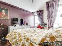 cozy bedroom with a queen-size bed, plenty of storage space and a TV in a 1-bedroom Paris luxury apa