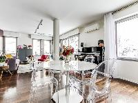stylish dining area with a table and designer acrylic clear chairs  in a 1-bedroom Paris luxury apar