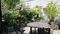 big terrace with potted plants and flowers, coffeetable and chairs in a 1-bedroom Paris luxury apart
