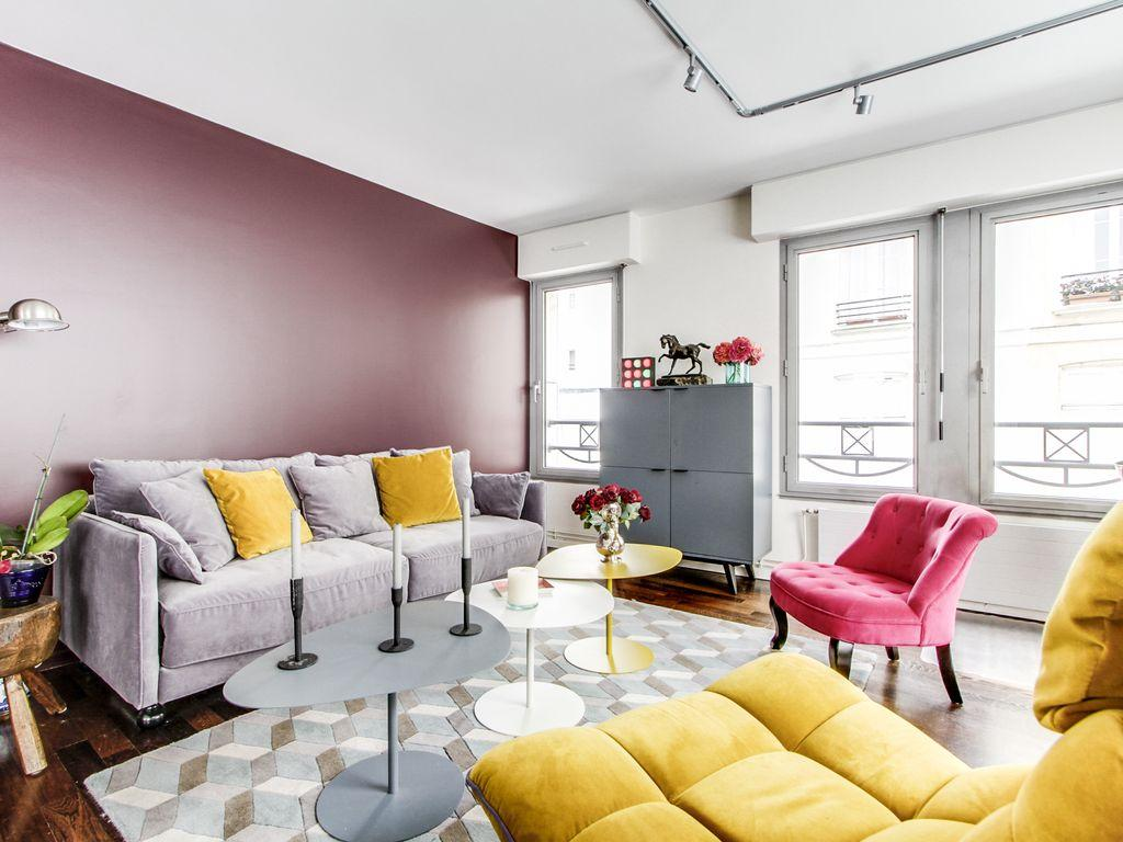 living room in yellow and rose hues with a double sized sofa-bed and three antique pianos in a 1-bed