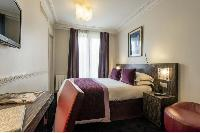 double bed, wooden study desk, and purple draped window in Hotel Waldorf Madeleine in Paris