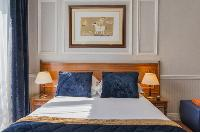 double bed, wooden study desk, and royal blue draped window in Hotel Waldorf Madeleine in Paris