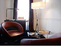 modern room with handful of tastefully made wooden furniture in Hotel Waldorf Madeleine in Paris