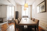 dining area with a wingback chair, a long wooden table, and six chairs in a 2-bedroom Paris luxury a