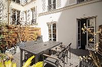 relaxing outdoor terrace with patio furniture in a 2-bedroom Paris luxury apartment