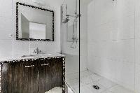 sleek white-tiled shower area in Paris luxury apartment