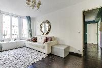 elegant open plan living with white sofa, furry cream carpet rug and gree draped windows in Paris lu