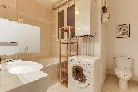 large bathroom with toilet and washing machine in Paris luxury apartment