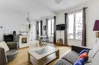 bright living area with a comfortable couch, a wooden centerpiece and huge widescreen TV in Paris lu