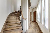 stairs and hallway lined with glass walls in Paris luxury apartment