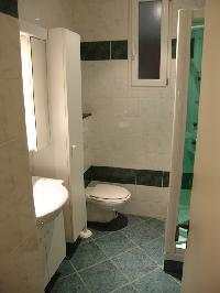 sleek bathroom with a nice shower stall with water massage selections and toilet in Paris luxury apa