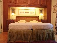 neatly stocked and cozy bedroom fitted with two twin beds joined to form one queen size bed in Paris