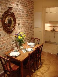 stylish brick-walled dining area with wooden table and chairs for 4 and well-equipped kitchen in Par