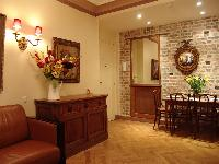 stylish brick-walled dining area with wooden table and chairs, wooden cabinets, and brown leather so