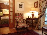 elegant armchairs with colorful prints and nightstand with lamp in Paris luxury apartment