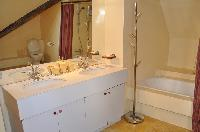 large bathroom with two sinks, full-sized mirror, washing machine and a dryer, a toilet, and a large