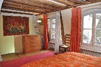 warm and bright master bedroom with two twin beds or a king size bed, red carpet rug, cabinet, red a