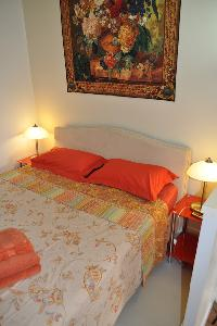 second bedroom with a queen size bed and a glass paned door leading to the terrace with a parasol, t