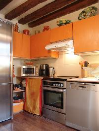 fully-equipped kitchen in tangerine hue and exposed beams in a 2-bedroom Triplex Paris apartment