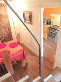 stairs, dining area and kitchen with wooden floor in a 2-bedroom Triplex Paris apartment