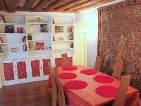 dining area for 6 with styish carpet, exposed beams and shelves in a 2-bedroom Triplex Paris apartme