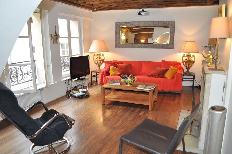 a warm and bright living room with original exposed beamed ceilings, parquet floors, large lovely so