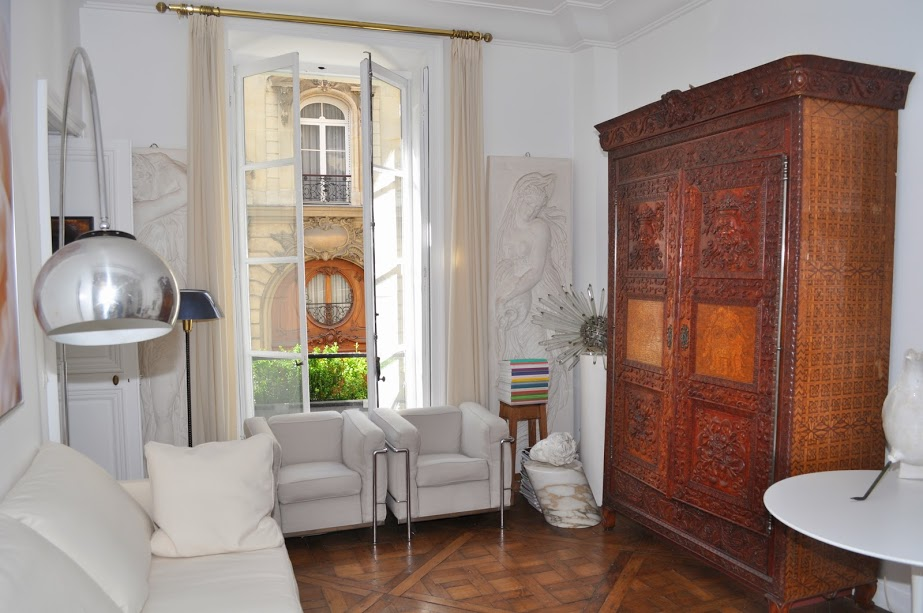 spacious, bright and airy living areawith white sofas and antique wooden cabinet in Paris luxury apa