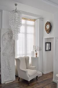 elegant white armchair beside a framed artwork and stylish chandelier in Paris luxury apartment