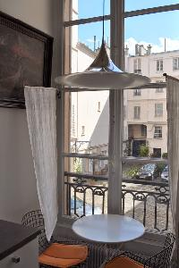 round coffee table for 2 beneath a ceiling lamp overlooking the courtyard in Paris luxury apartment