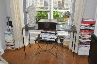 glass study desk, bust, and tower of books in Paris luxury apartment