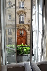 French glass windows open out to the quiet and beautiful courtyard garden below in Paris luxury apar