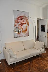white sofa, arc floorlamp,and framed artwork in Paris luxury apartment