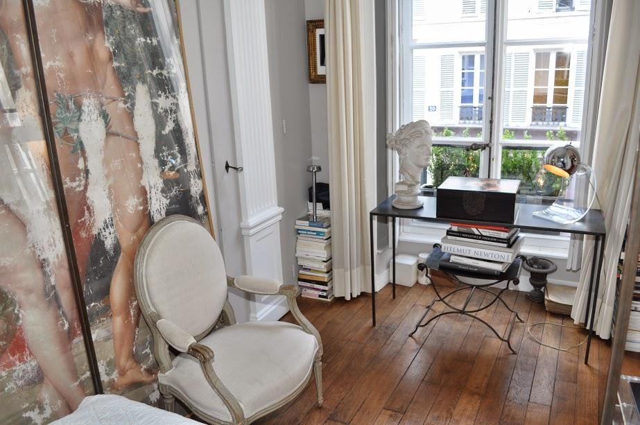 classy bedroom with elegant white armchair and framed artwork in Paris luxury apartment