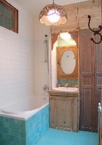 turquoise-tiled bath with ceiling lamp in Paris luxury apartment