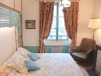charming bedroom with a queen size bed, floral draped window, and brown armchair in Paris luxury apa