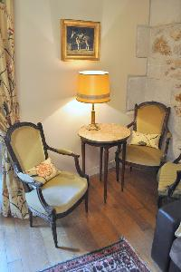 cream armchairs with nightstand and lamp in Paris luxury apartment