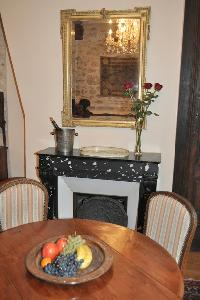 wooden round table for 4, elegant chandelier, and ornamental fireplace beneath elaborate mirror in P