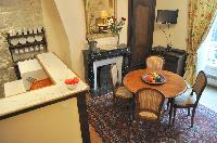classy kitchen and dining area with wooden round table for 4 in Paris luxury apartment