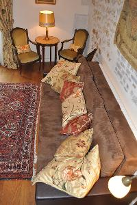 brown long sofa with floral throw pillows and armchairs with nightstand and lamp in Paris luxury apa