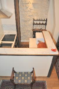 well-equipped kitchen with counter and stool in Paris luxury apartment
