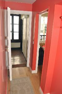 hallway with red walls and beautifully lined parquet floors in Paris luxury apartment