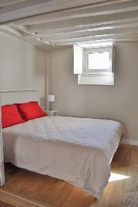 queen size bed and exposed beam in Paris luxury apartment
