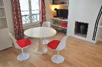 dining area with white round table and red chairs in Paris luxury apartment