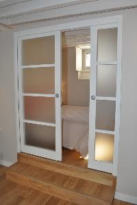 white sliding door opens to the bedroom in Paris luxury apartment