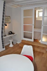 dining area with mini study area, sliding door access to the bedroom in Paris luxury apartment