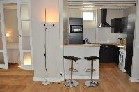well-equipped kitchen with breakfast bar and stools in Paris luxury apartment