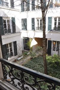 two large windows that open onto the quiet courtyard in Paris luxury apartment