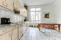 well-equipped kitchen with dining table and chairs in a 4-bedroom Paris luxury apartment