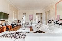 elegant living area with L-shaped sofa, chairs, wooden floor, and lamps in a 4-bedroom Paris luxury