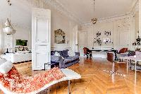 comfortable sitting area with comfortable sofa, study desk, chairs, and paintings in a 4-bedroom Par